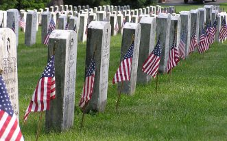 Memorial Day - Veteran's Cemetery with American Flags at each grave stone.